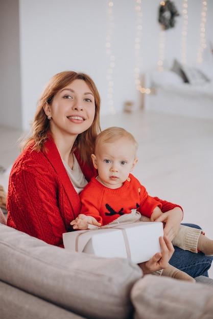 ソファに座ってクリスマスプレゼントを開梱する彼女の赤ん坊の息子を持つ母親 無料写真
