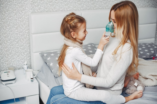 Mother with her illnes daughter in a bedroom Free Photo