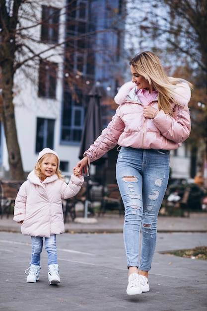 Mother with her little daughter dressed in warm cloth aoutside the street Free Photo
