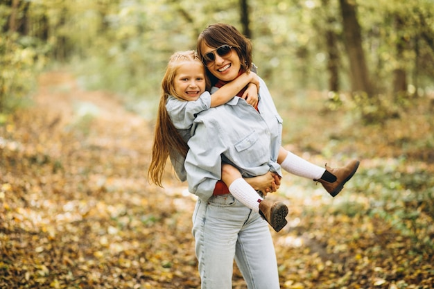Mother with her little daughter in forest full of golden leaves Free Photo