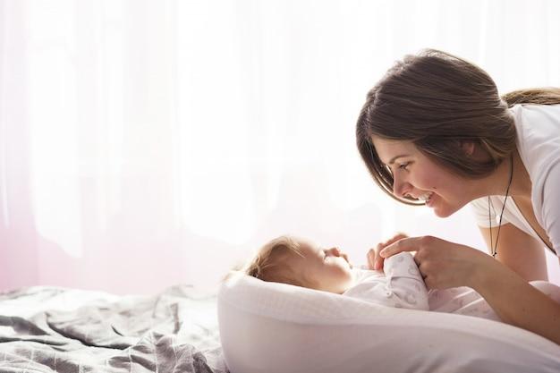 生まれたばかりの息子を持つ母親は、窓から出てくる日光の光線でベッドに横たわりました Premium写真