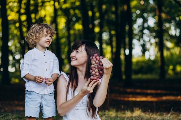 森でピクニックをしている彼女の息子を持つ母 無料写真