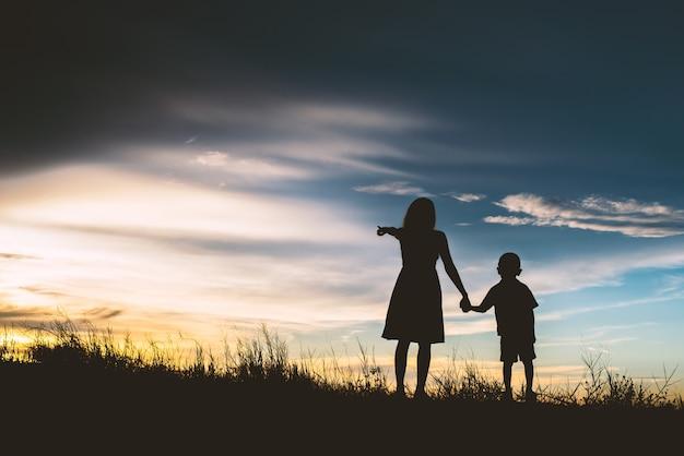 Madre con il suo figlio che punta verso l'orizzonte Foto Gratuite