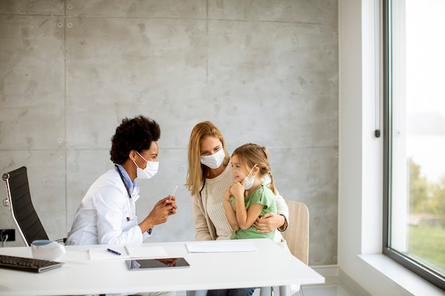 Mother with his little daughter at the pediatrician examination by african american female doctor Premium Photo