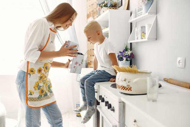 Madre con bambini piccoli cucinare a casa Foto Gratuite