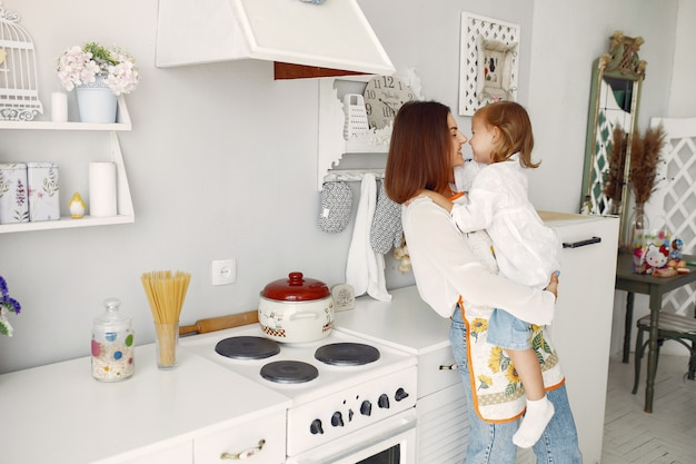 自宅で料理の小さな娘を持つ母 無料写真