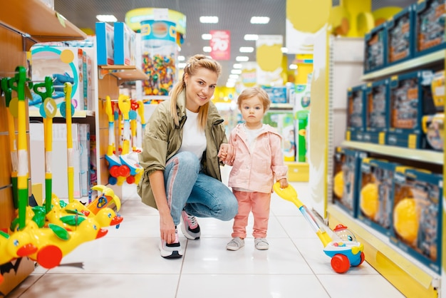 Premium Photo   Mother with little daughter in kids store. mom and child  together choosing toys in supermarket