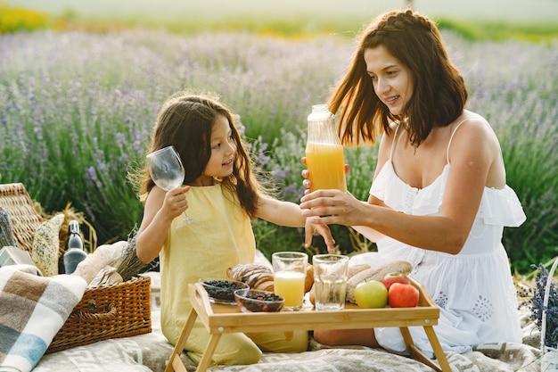 Madre con la piccola figlia sul campo di lavanda. bella donna e bambino sveglio che giocano nel campo del prato. famiglia in un picnic. Foto Gratuite