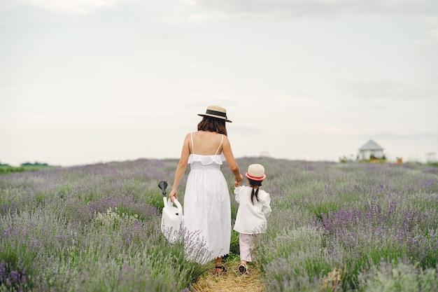 ラベンダー畑に小さな娘を持つ母。美しい女性と牧草地で遊ぶかわいい赤ちゃん。夏の日の家族の休日。 無料写真