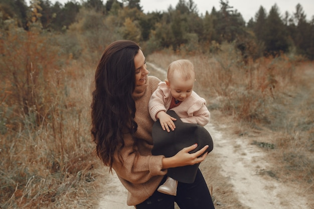 Mother with little daughter playing in a autumn field Free Photo