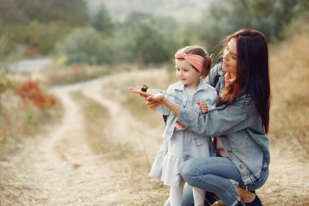 Mother with little daughter playing in a field with a butterfly Free Photo