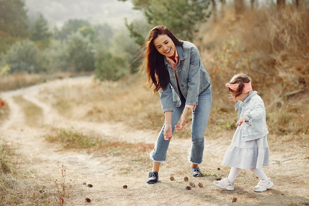 Mother with little daughter playing in a field Free Photo