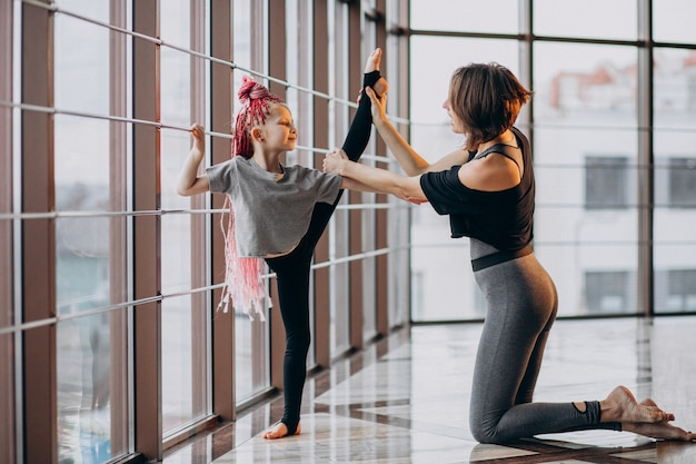 Mother with little daughter practicing yoga by the window Free Photo
