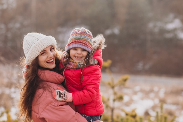 Mother with little daughter in a winter forest Free Photo