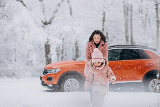 Mother with little daughter in a winter park by car Free Photo