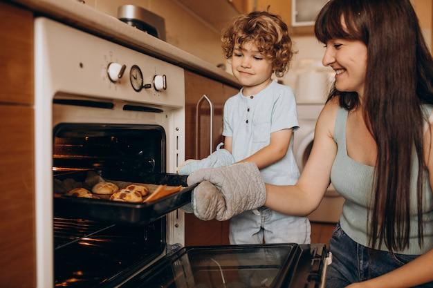 オーブンでクッキーを焼く幼い息子を持つ母 無料写真