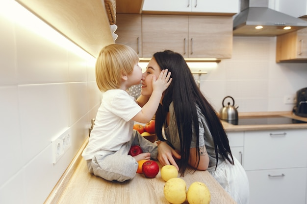 Mother with little son eating fruits in a kitchen Free Photo