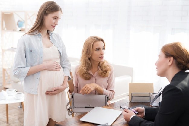Mother with pregnant daughter in doctor office. Premium Photo