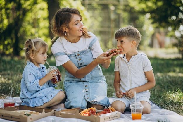 아들과 딸이 공원에서 피자를 먹는 어머니 무료 사진