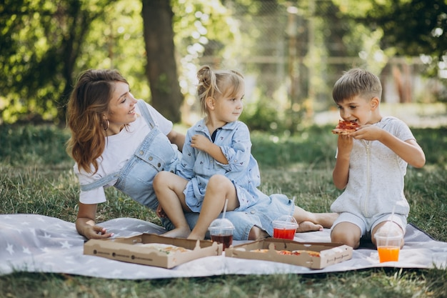Mother with son and daughter eating pizza in park Free Photo
