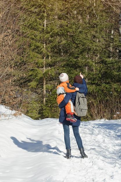Мать с сыном на руках и рюкзак стоит Premium Фотографии