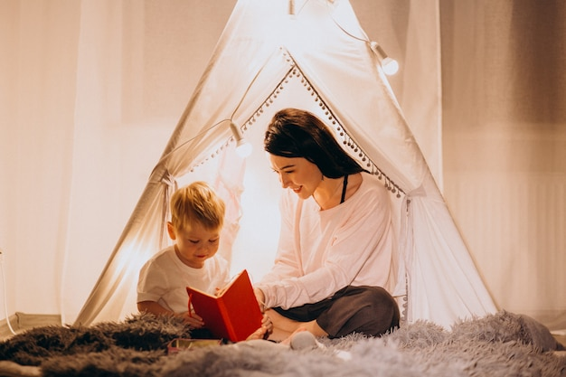 Mother with son sitting in cozy tent with lights at home on christmas Free Photo