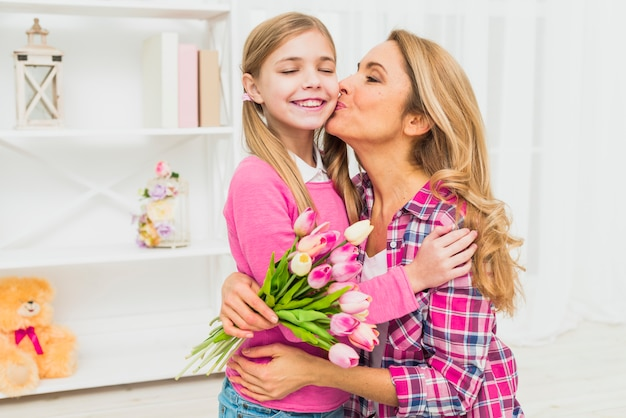 Mother with tulips kissing daughter on cheek Free Photo