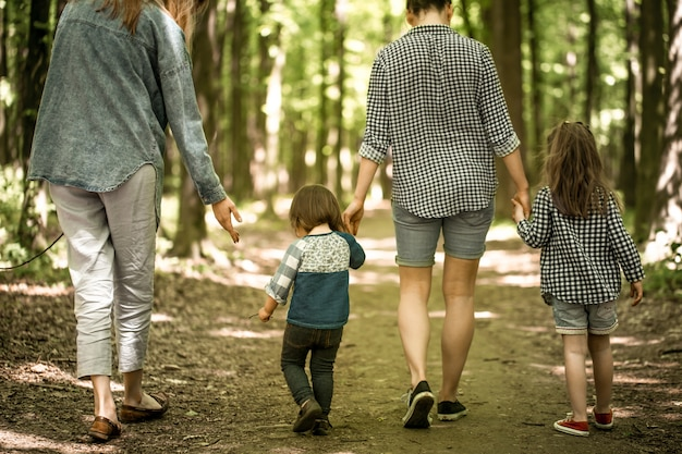 Mother with young daughters walk in the woods Free Photo