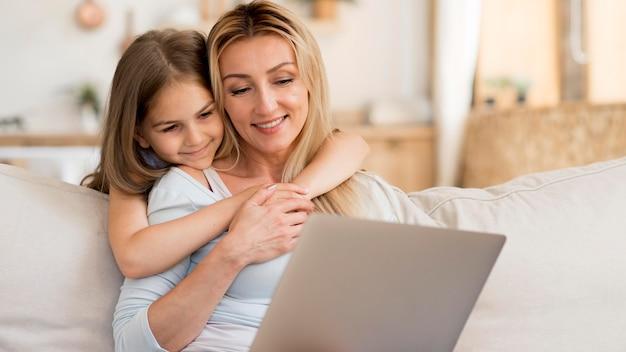 Мать работает на ноутбуке из дома с дочерью, обнимая ее Бесплатные Фотографии