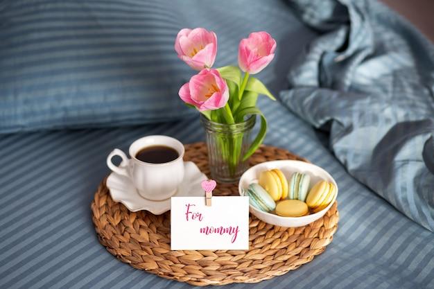 День матери. завтрак в постель для мамы. завтрак в постель с картой и чашкой кофе. macarons с чашкой кофе. доброе утро. открытка для мамы. тюльпаны неубранная пастель с завтраком Premium Фотографии