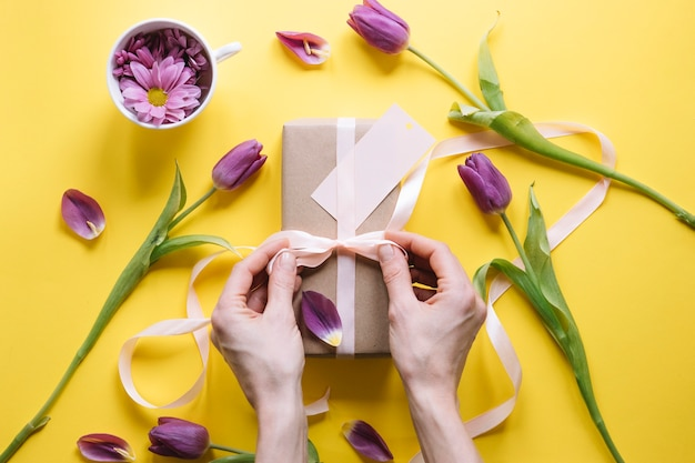 Mothers day composition with hands preparing gift box Free Photo
