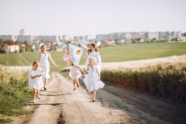 Mothers with daughters playing in an autumn field Free Photo