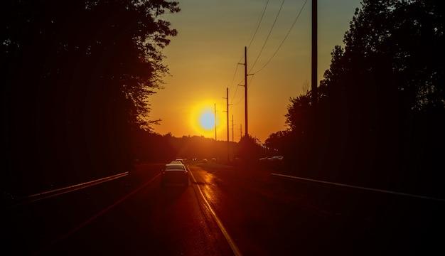 Motion blur highway traffic in sunset road running through forest