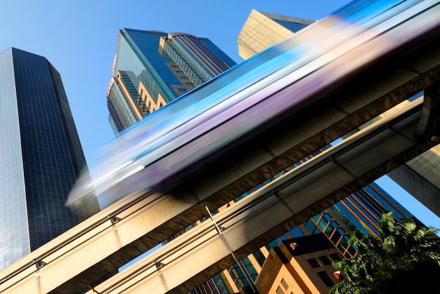 Motion blur of a skytrain speeding through a modern business district Free Photo