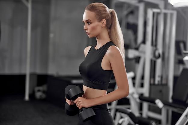 Motivated blonde raising dumbbells in gym. Premium Photo