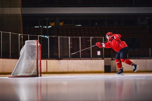 Мотивированная тренировка хоккеиста стрельбе по воротам при катании на льду. Premium Фотографии