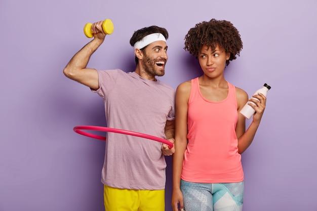 Il giovane motivato si esercita con l'hula hoop, solleva il manubrio, ha un'espressione felice, indossa una fascia bianca e una maglietta e una donna scontenta sta con una bottiglia d'acqua, ha un allenamento fitness Foto Gratuite