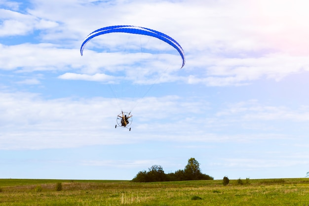 Moto paraglider flying over a field in a blue sky with clouds. Premium Photo