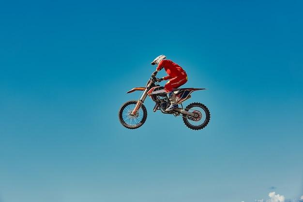 Концепция мотокросса, байкер едет по бездорожью, делая экстремальные лыжи. Premium Фотографии