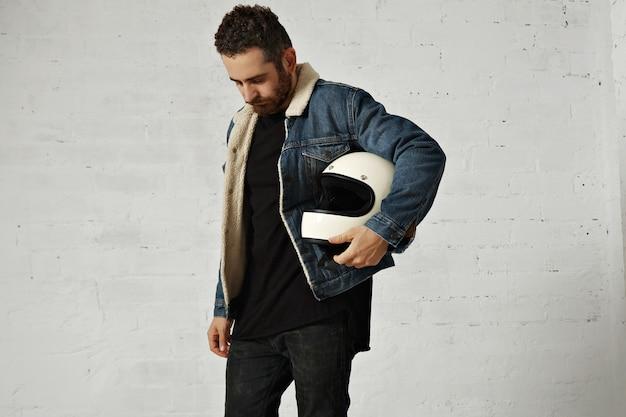 Motociclista indossa giacca di jeans shearling e camicia henley nera vuota, tiene il casco da motociclista beige vintage, guardando in basso, isolato al centro del muro di mattoni bianchi Foto Gratuite