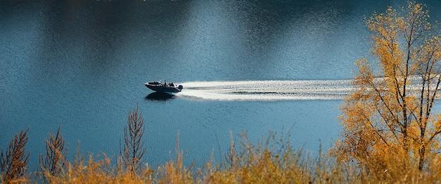 モーターボートは、秋の森のある丘の間を流れる青い川の真ん中で移動します。 Premium写真