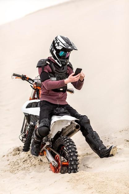 ヘルメットブラウジング携帯電話を持つバイクライダー 無料写真