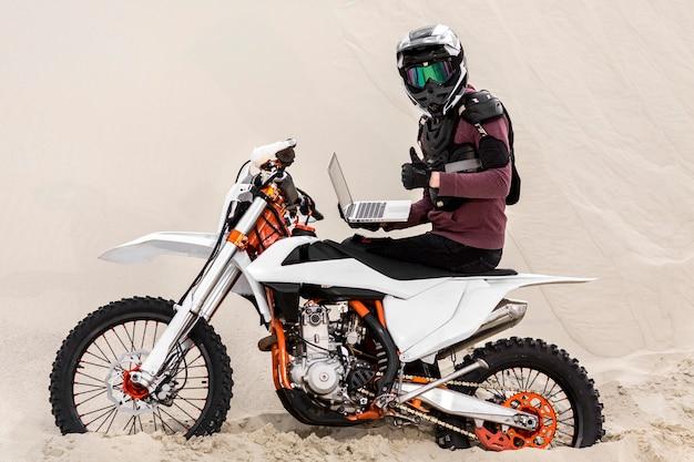 ラップトップを保持しているヘルメットを持つバイクライダー 無料写真