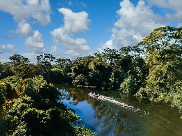 Motoscafo nel lago circondato da bellissimi alberi verdi sotto un cielo nuvoloso Foto Gratuite