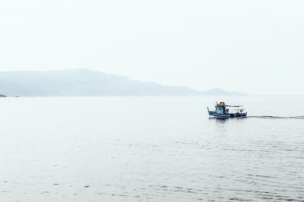 Моторная лодка на море в окружении гор, окутанных туманом Бесплатные Фотографии