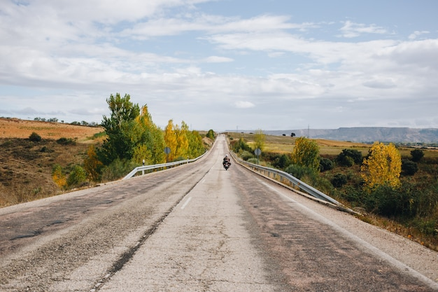 Motorcycle rider on empty country road Free Photo