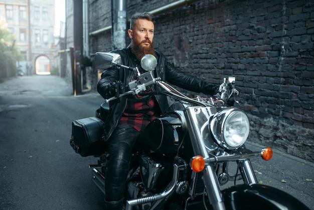 Мотоциклист в кожаной куртке позирует на классическом чоппере. винтажный велосипедист на мотоцикле, образ жизни свободы Premium Фотографии