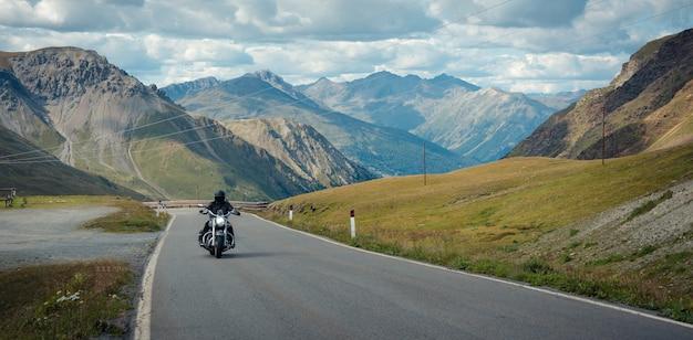 A motorcyclist is going through the stelvio pass. italy Premium Photo