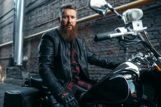 Мотоциклист позирует на классический чоппер, байкер. винтажный велосипедист на мотоцикле, образ жизни свободы Premium Фотографии