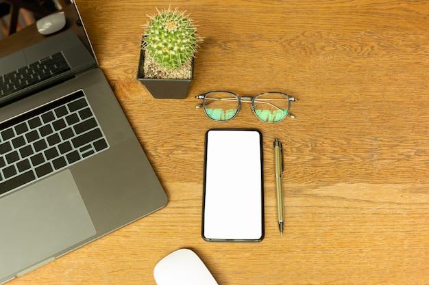 ノートパソコン、眼鏡、ペン、コンピューターmoueseのオフィスデスクの平面図です。 Premium写真